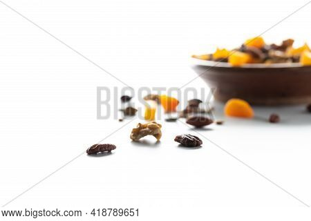 Trail Mix Scattered On A Table With A Bowl Of Trail Mix In Soft Focus In Behind Against A Bright Whi