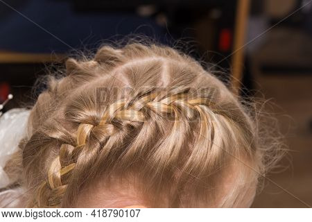 The Girls Hairstyle Is Braided In Two Braids On The Sides Of The Head In Close-up. Hair Styling Is D