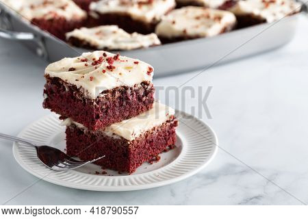 Two Red Velvet Squares In A Stack On A Plate With Other Squares In Soft Focus In Behind And Copy Spa