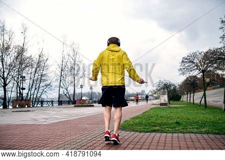 The Athlete Jumps On A Racecar In The Morning In Sports Jacket And Shorts. A Cyclist Passes. The Emb