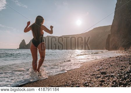 Happy Carefree Sensual Woman With Long Hair In Black Swimwear Posing At Sunset Beach. Silhouette Of