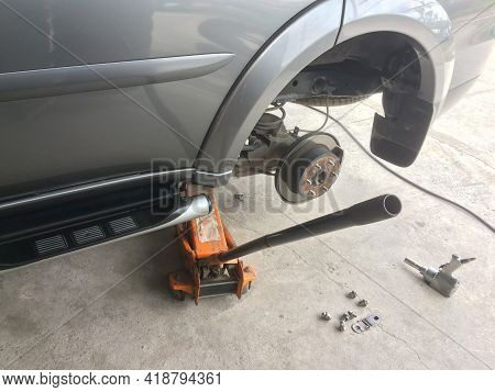 Car To Remove The Wheel For Maintenance With Body Lift Equipment And Pneumatic Gun.