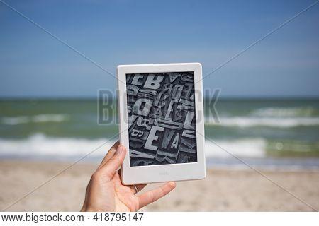 Berdyansk, Ukraine - 06.11.2020: Kindle Electronic Book Device At Female Hand On Seaside Background,