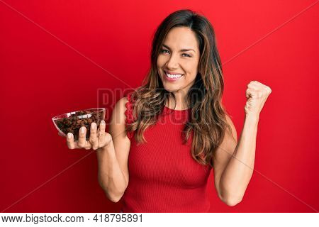 Young latin woman holding bowl with raisins screaming proud, celebrating victory and success very excited with raised arm