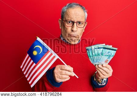 Handsome senior man with grey hair holding malaysia flag and malaysian ringgit banknotes skeptic and nervous, frowning upset because of problem. negative person.