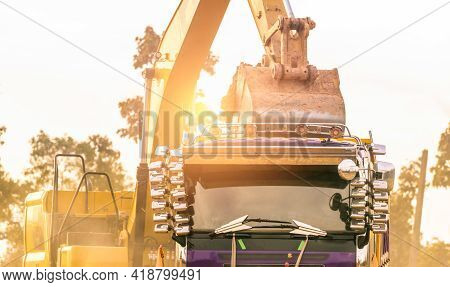 Backhoe Working By Digging Soil At Construction Site And Loading To The Truck. Bucket Of Backhoe Tra