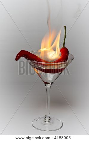 The fire of a red hot chili pepper in a cocktail