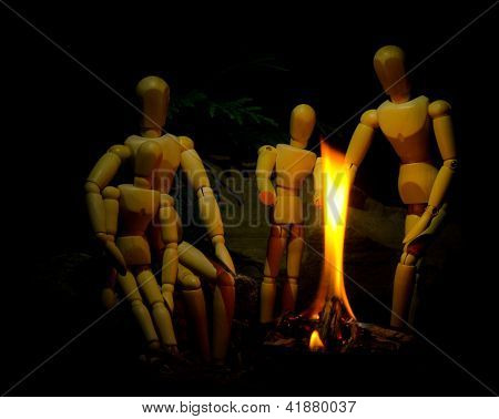 Family Of Four Wooden People Happily Enjoying Campfire