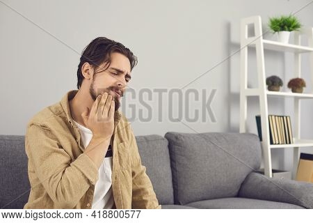 Upset Young Man Suffering From Severe Toothache And Touching Cheek With Grimace Of Pain