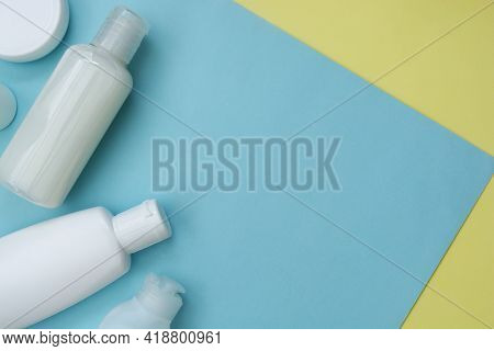 Creative Concept Of Recycling Cosmetics Bottles On Blue And Yellow Background, Copy Space For Text