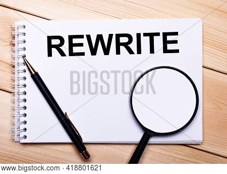 On A Light Wooden Background Lie A Pen, A Magnifying Glass And A Notebook With The Text Rewrite
