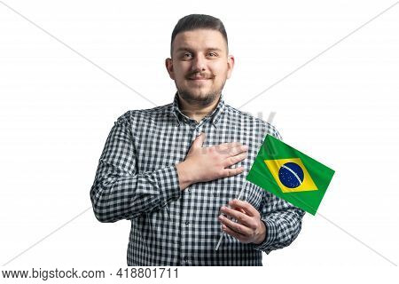 White Guy Holding A Flag Of Brazil And Holds His Hand On His Heart Isolated On A White Background Wi