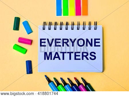 The Words Everyone Matters Written In A White Notebook On A Beige Background Near Multi-colored Mark