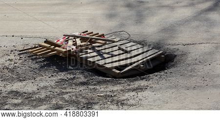 A Pothole In The Asphalt Road Surface Is Covered With Wooden Pallets