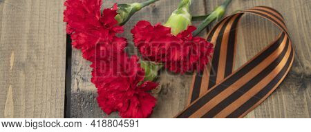 Banner With Three Red Carnations With A St. George Ribbon On A Wooden Background. Georgievsk Ribbon