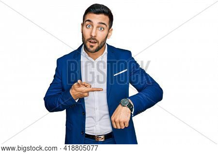 Young hispanic man wearing business jacket in hurry pointing to watch time, impatience, upset and angry for deadline delay