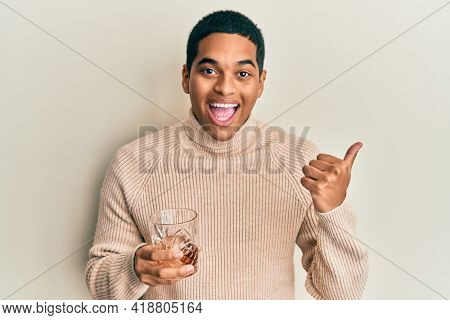 Young handsome hispanic man drinking glass of whisky pointing thumb up to the side smiling happy with open mouth
