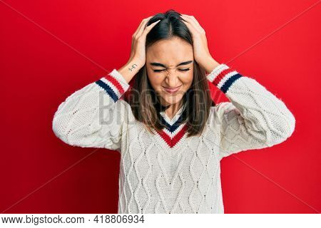Young brunette girl wearing casual student sweater suffering from headache desperate and stressed because pain and migraine. hands on head.