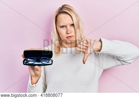 Beautiful caucasian blonde woman holding glasses in eyewear case with angry face, negative sign showing dislike with thumbs down, rejection concept