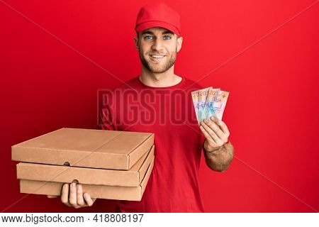 Young caucasian man holding delivery box and swiss franc banknotes smiling with a happy and cool smile on face. showing teeth.