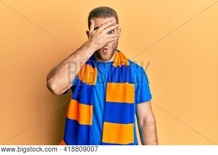 Young caucasian man football hooligan cheering game peeking in shock covering face and eyes with hand, looking through fingers afraid