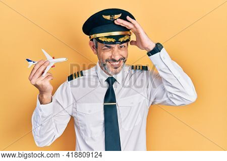 Handsome middle age man with grey hair wearing airplane pilot uniform holding toy plane stressed and frustrated with hand on head, surprised and angry face