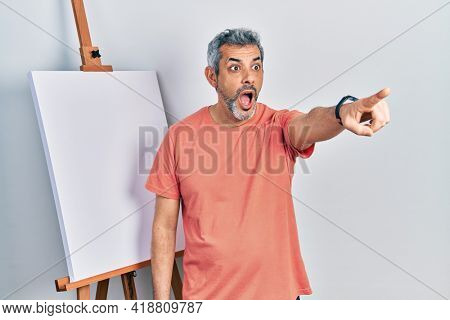 Handsome middle age man with grey hair standing by painter easel stand pointing with finger surprised ahead, open mouth amazed expression, something on the front