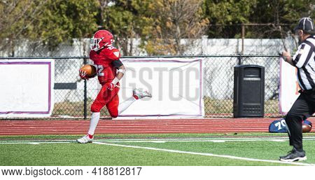 A High School Football Player In Ared Uniform Is All Alone As He Is Running Along The Sideline For A