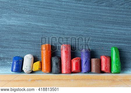Small Colored Wax Crayons On A Blackboard. Children's Hobby And Creativity Concept