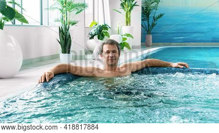 A Man Relaxes In A Pool With Hydro Massage In The Aquazone Of A Spa Center. Relax In The Pool At You