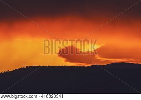 Atmospheric Landscape With Dark Silhouette Of Mountain With Trees On Background Of Vivid Orange Dawn