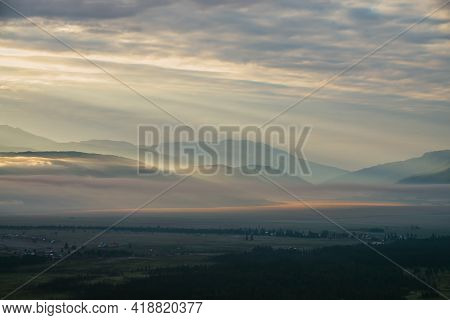 Scenic Mountain Landscape With Orange Lilac Low Clouds Above Village Among Mountains Silhouettes Und