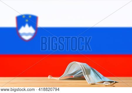 A Medical Mask Lies On The Table Against The Background Of The Flag Of Slovenia. The Concept Of A Ma