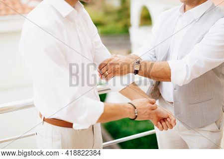 The Groom Pulls Up The Sleeves Of His Shirt While Preparing For The Wedding Ceremony, The Best Man H