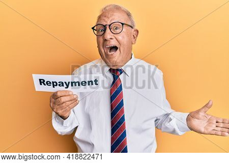 Senior caucasian man holding repayment word paper celebrating achievement with happy smile and winner expression with raised hand