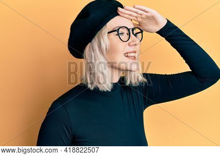 Young blonde girl wearing french look with beret very happy and smiling looking far away with hand over head. searching concept.