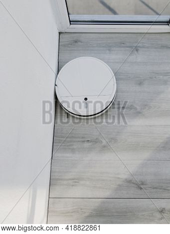 White Robot Vacuum Cleaner Cleans The Floor. Home Cleaning With An Electric Vacuum Cleaner. Top View