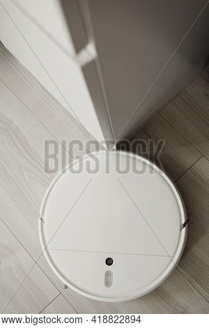 Robotic Vacuum Cleaner On Laminate Wood Floor In Living Room. Vacuum Cleaner For Daily Cleaning