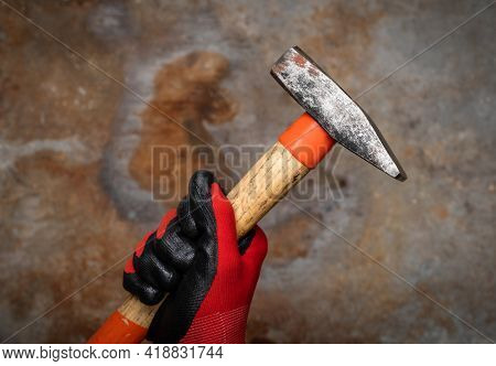 Person wearing protective glove holding a hammer against rusty metal background