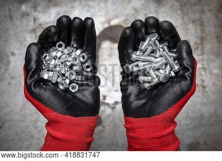 Person wearing protective gloves holding a handful of bolts and nuts against metal background
