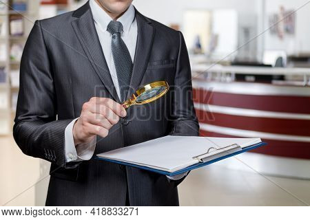 Criminal Investigation Study Concept. Lawyer Examining A Document With A Magnifier On A Blurred Back