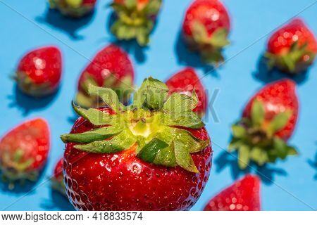 Delicious Red Strawberry In Foreground. In Blurred Background Pattern Of Ripe Strawberries With Gree