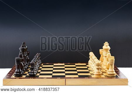 Wooden Chess. Chess Pieces Are Located On A Chessboard. On A White Table With A Black Background. Cl