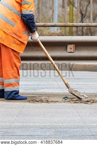 A Janitor In An Orange Reflective Uniform Shovels Loose Sand From The Road Between The Lanes Under A