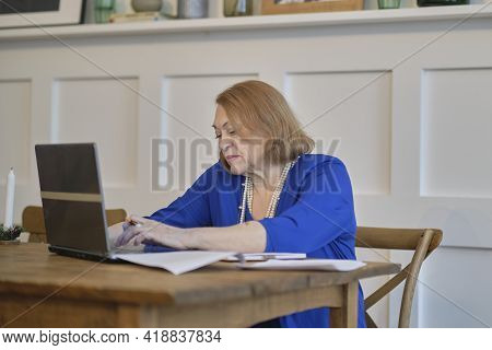 Elder Woman Using A Laptop Computer At Home. Mature Lady Sitting At Work Typing A Notebook Computer