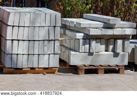 Massive Textured Concrete Curbs Are Stacked On Wooden Pallets At The Construction Site, Stored For R