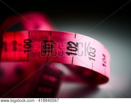 Close Up Tailor Measuring Tape On White Table Background. White Measuring Tape Shallow Depth Of Fiel