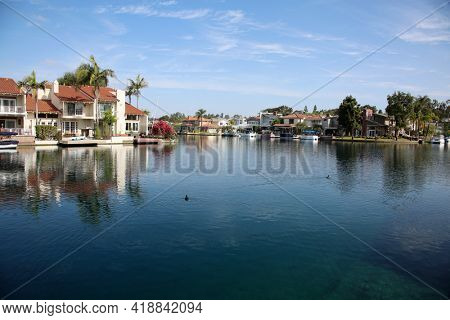 April 18, 2021 Lake Forest, California USA - One of Lake Forest Lakes with Boats and Homes on the water front. View of Homes and boats docked in Lake Forest, California.  Editorial Use Only.