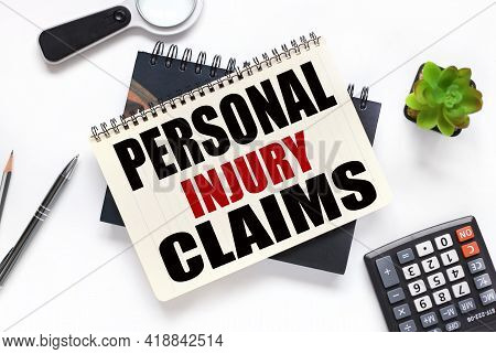 Personal Injury Claims. An Open Notebook Lies On A Closed Notebook Near A Calculator And A Magnifyin