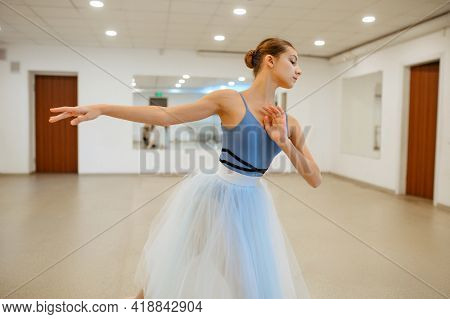 Young ballerina rehearsing at the barre in class